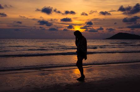 silhouette of girl sitting on beach Imagens