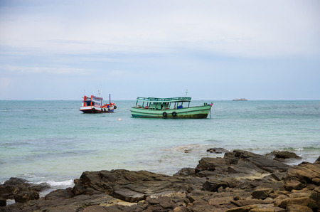passenger boat in sea with stone beach