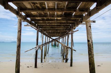 under of old bridge on beach