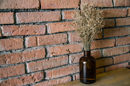 dry flower in bottle on table with brick wall