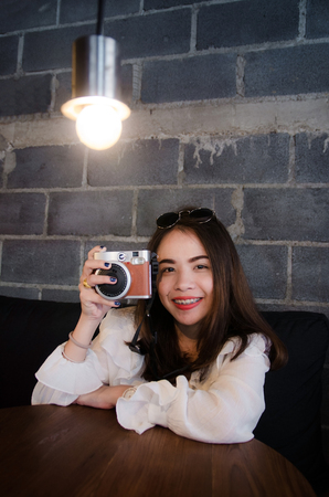 asian pretty girl sitting in cafe is holdind film camera Imagens