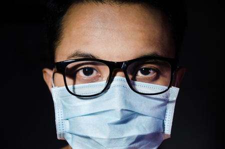 close up of young asian man wearing hygienic mask annd glasses with dark blackground