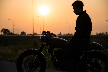 silhouette of man riding vintage motorcycle cafe racer style on sunset scene Imagens