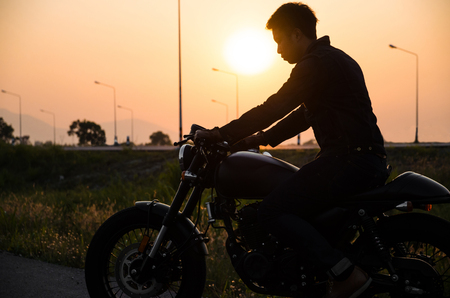 silhouette of man riding vintage motorcycle cafe racer style on sunset scene holding healmet