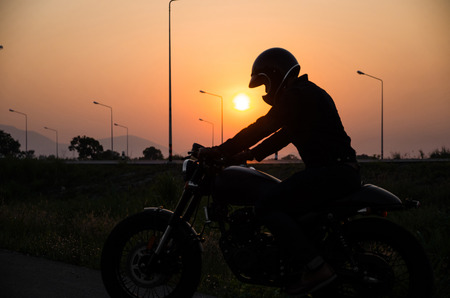 silhouette of man riding vintage motorcycle cafe racer style with helmet on sunset scene Imagens