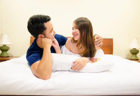 asian couple lying on bed ,eye contact together Imagens