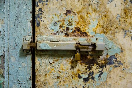 old latch is locking pale door in front view Stock Photo