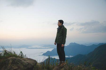 junger Mann, der auf einem Hügel steht, trägt einen grünen Mantel Standard-Bild