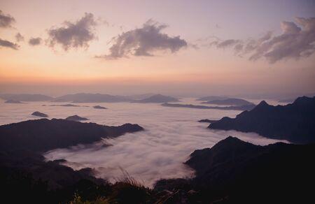 sunrise with dark mountain and mist Stock Photo