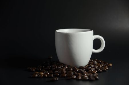 white cup with coffee beans in dark light