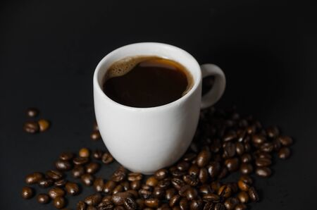 white coffee cup with coffee beans in dark light
