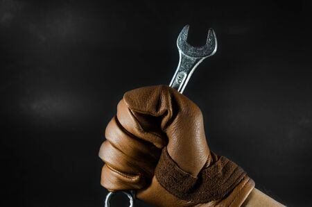 a wrench was holding by leather glove man hand in dark light