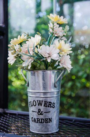 flower in aluminium pot on black steel shelves