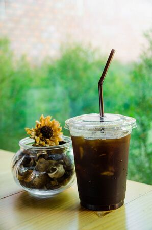 glass of iced coffee on wooden table with fry yellow flower in cafe Stock Photo
