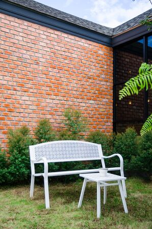 white chair in garden with brick wall background Stock Photo