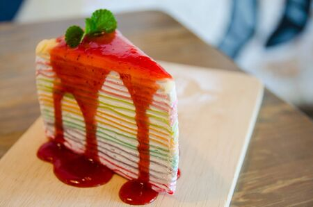 close up of rainbow crepe cake on wooden plate Stock Photo