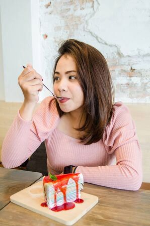 Asian girl is eating crepe cake