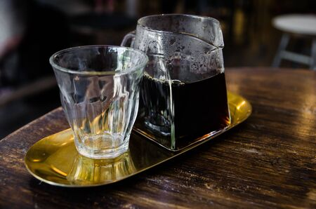black coffee in glass pitcher on golden plate on wooden table