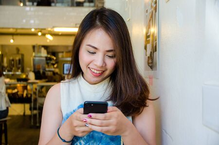 asian girl holding phone in coffee cafe with smile face