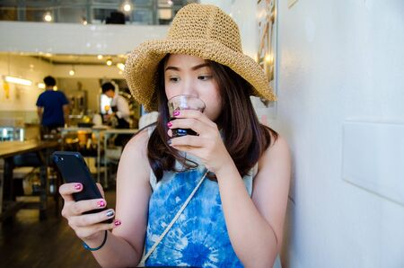 asian girl is holding phone and drinking in coffee cafe