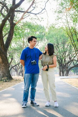 asian couple are sling camera, are walking in park, and hold hand together