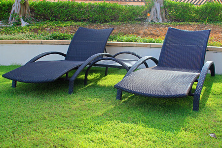 loungers: Wicker sun loungers on the grass in the sun Stock Photo
