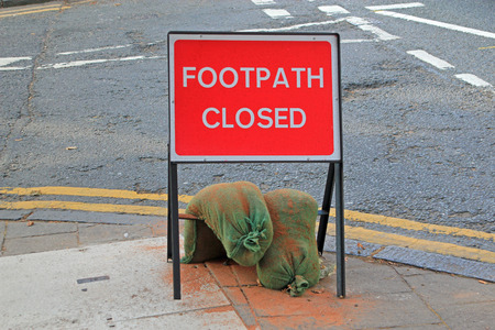 held down: Road sign for a closed footpath held down by sandbags