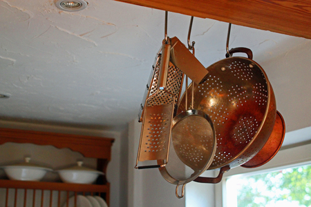 country kitchen: Country kitchen with close-up of kitchen utensils hanging from a beam with plate rack in the background
