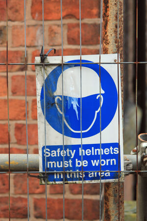 stating: Blue sign stating safety helmets must be worn symbolizing danger and safety equipment