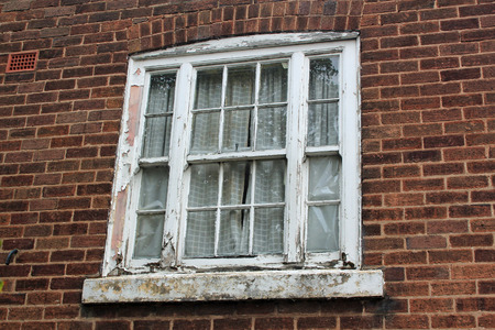 pealing: White window frame with pealing paint in a brick wall