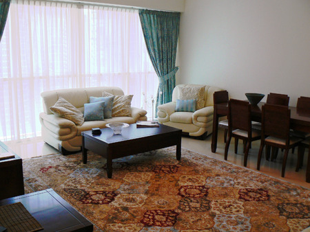 Living room of a show flat with oriental rug and leather sofa Editorial