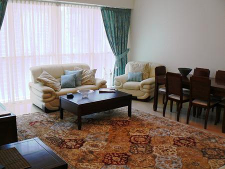 Wohnzimmer einer Musterwohnung mit orientalischen Teppich und Ledersofa Standard-Bild - 33579217