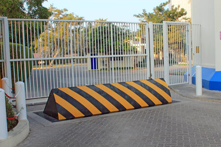 security barrier: Yellow and black security barrier in front of security gates symbolizing protection, security and potential threats Stock Photo