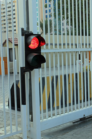security barrier: Red traffic light at a security gate with yellow and black security barrier symbolizing protection, security and potential threats Stock Photo