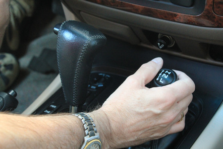 4 wheel: Changing gear in a car symbolizing safety, 4 wheel drive and hands off the steering wheel Stock Photo