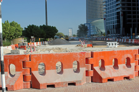 road works: Close-up of orange barriers designating road works with modern buildings in the background