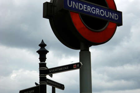 knightsbridge: Signs for the London Underground, Knightsbridge and Buckingham Palace against a cloudy British sky