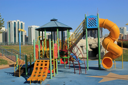 climbing frame: Inner city childrens play area with colorful slides and climbing frame against a backdrop of a modern city Stock Photo