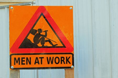 Red warning triangle on a yellow background with picture of a workman with a shovel over his shoulder and the words Men at Work symbolizing road works, construction, workmen, danger and safety procedures