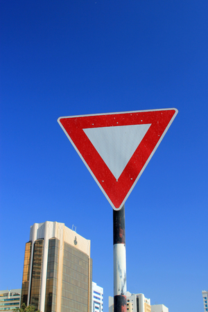 give way: Yield triangle traffic sign against a blue sky with modern buildings in the background symbolizing the need to give way Stock Photo