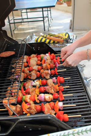 al fresco: Close up of a woman turning kebab skewers with chicken, peppers, onions and tomatoes on the BBQ symbolizing al fresco cooking, BBQ eating and summer Stock Photo