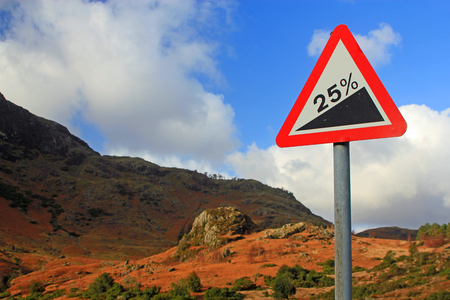 upward climb: Street sign showing a 25 gradient with mountainous background symbolizing a sharp increase, upward climb and struggle