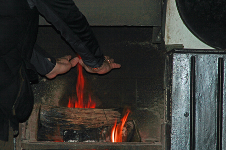 fire surround: Man warming his hands on an old fashioned pub open fire with roaring logs and traditional fire surround