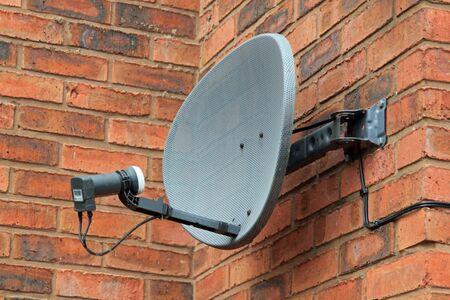 satellite dish: Close up of a satellite dish on a brick wall