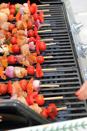 al fresco: Close up of woman putting kebab skewers with chicken, peppers, onions and tomatoes on the BBQ symbolizing al fresco cooking, BBQ eating and summer