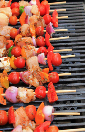 al fresco: Close up of kebab skewers with chicken, peppers, onions and tomatoes on the BBQ symbolizing al fresco cooking, BBQ eating and summer Stock Photo