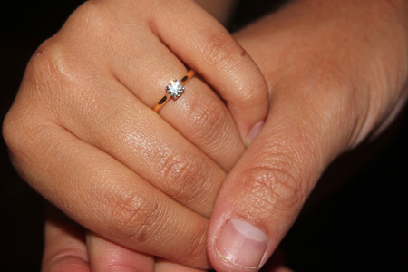engagement ring: Close up of mans hand holding a womens hand showing off an engagement ring against a pure black background symbolizing relationships, engagement, love and marriage