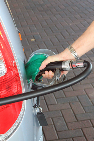 unleaded: Close up of man filing up a car with fuel symbolizing the cost of fuel, cars that run on petrol or diesel rather than electric, reliance on cars rather than other modes of transport and the environmental impact of unleaded petrol Stock Photo