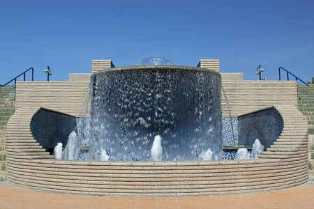 water feature: Modern water fountain in a park with setps either side and walkways against a backdrop of blue sky demonstrating an ornamental water feature, modern parks and the beauty of pure fresh water Stock Photo