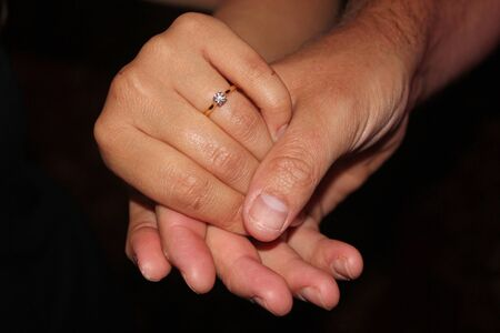 women's hand: Mans hand holding a womens hand showing off an engagement ring against a pure black background symbolizing relationships, engagement, love and marriage